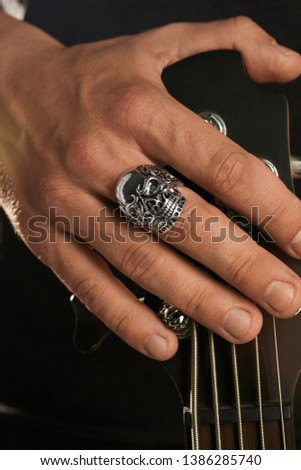 Cropped closeup shot of man's hand, touching headstock of guitar. The guy is wearing massive ring with blacking in view of a skull. The man is wearing black clothes, posing over the dark background. Foto stock ©