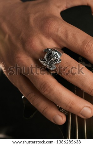 Cropped closeup shot of man's hand, touching headstock of guitar. The guy is wearing signet-ring in view of eagle. The man is wearing black clothes, posing on dark background. Trendy men's accessory. Foto stock ©