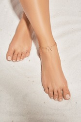Cropped front shot of girl's legs with french pedicure, wearing golden ankle bracelet, decorated with golden insertion in view of tied bow. The lady is crossing her legs, lying on the sandy platform.