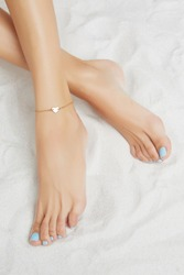 Cropped front shot of girl's legs with pale blue pedicure, wearing golden ankle bracelet, decorated with golden insertion in view of heart. The lady is crossing her legs, lying on the sandy platform.