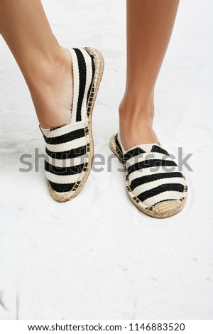 69406c57e4 Cropped front view of woman's legs in striped espadrille shoes, isolated on  a white background