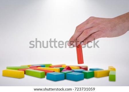 Cropped hand arranging blocks against grey background #723731059