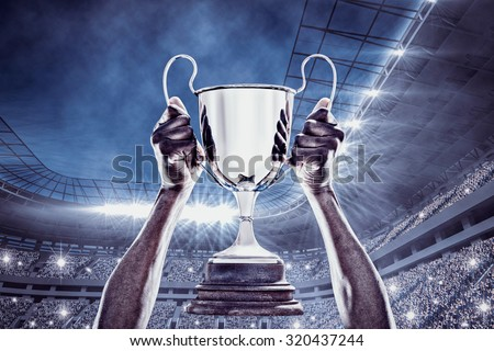 Cropped hand of athlete holding trophy against football stadium