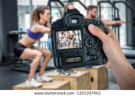 Cropped hand of photographer holding camera  against three muscular athletes doing jumping squats