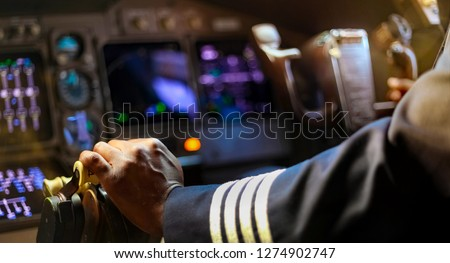 Cropped Hands of African Pilot flying a commercial airplane, cockpit view close up of hands #1274902747