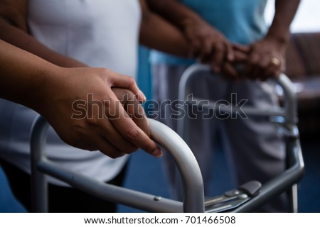 Cropped hands of nurse assisting woman in walking with walker at retirement home