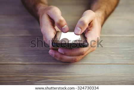 Cropped imafe of a person holding smartphone at wooden desk #324730334