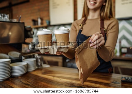 Cropped image, barista is working in coffee shop, young woman is standing behind the bar counter, making coffee, take away. Foto d'archivio ©