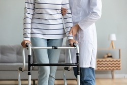 Cropped image caregiver helping to disabled aged female patient walk with walker physical therapist teach her, supporting during exercise therapy. Nursing at home, aftercare and physiotherapy concept