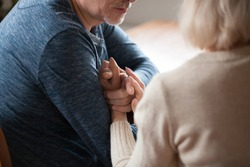 Cropped image close up people holding hands, loving old spouses middle aged wife and husband sitting close to each other touch arms, feeling tenderness and love. Endearment support and trust concept