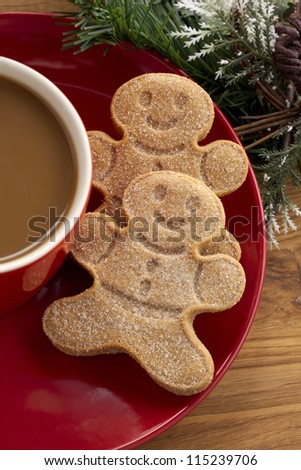 Cropped image gingerbread cookies in red saucer with coffee cup.