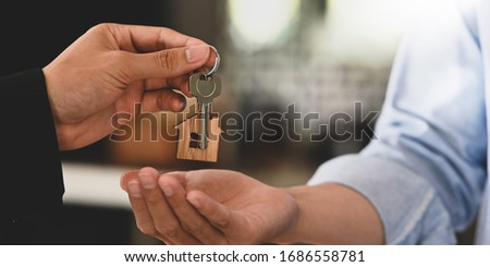 Cropped image Hands of real estate agent offering/giving a house key to smart man in blue shirt while standing together over modern bank as background. Broker/Seller/Dealer concept.