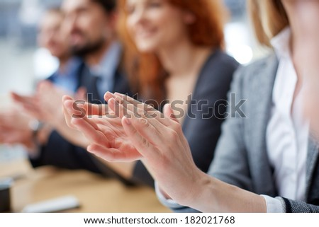 Cropped image of a businessperson applauding on the foreground