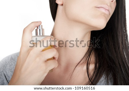 Cropped image of a cute young woman with a perfume bottle in her hand.