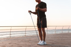 Cropped image of a fit sportsman doing exercises with expander at the seaside