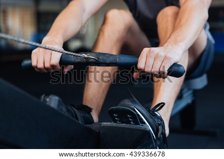 Cropped image of a fitness man using rowing machine in the gym