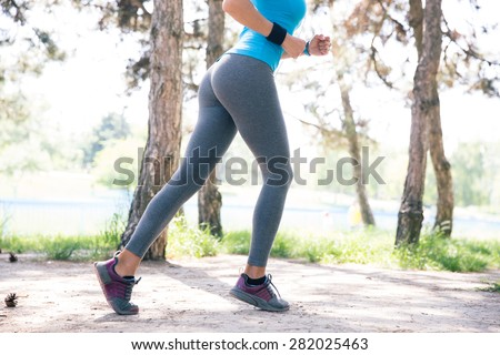 Cropped image of a fitness woman running outdoors in park