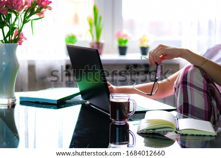 Cropped image of a girl or woman working on quarantine from home on the kitchen wearing pijama.Home office or distance learning concept. Freelance or e-learning.Coffee break.
