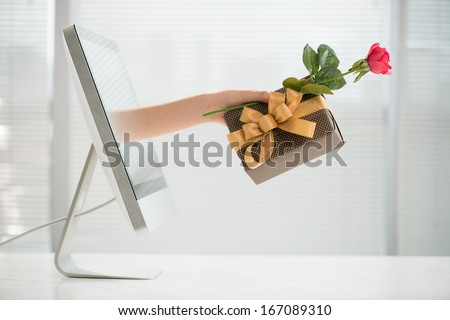 Cropped image of a human hand with a giftbox and a red rose from the computer screen
