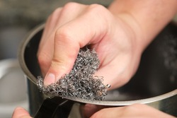Cropped image of a man hands washing a pot or doing the dishes with a stainless steel sponge scrubber. Cleaning household chores.