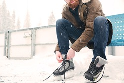 Cropped image of a man tying shoelace on ice skates outdoors