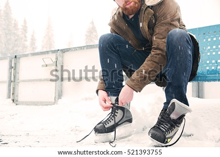 Cropped image of a man tying shoelace on ice skates outdoors stock photo