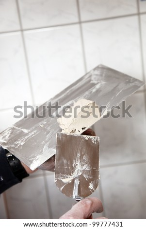 Cropped image of a man working with a metal spatula and prepared grout or adhesive when doing tiling in a home interior