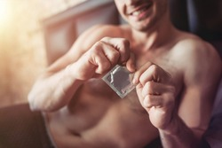 Cropped image of a smiling man holding condom in hand while lying on bed.