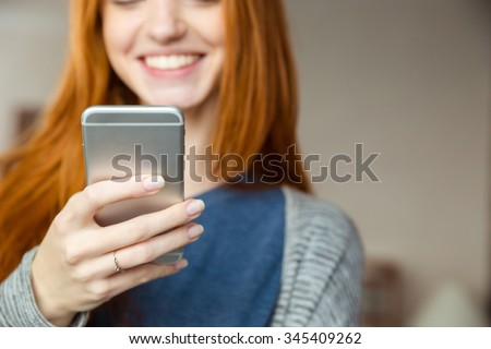 Cropped image of a smiling redhead woman using smartphone