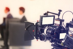 Cropped image of a Video of the interview. Television equipment, camcorder with LCD screen, lighting equipment.