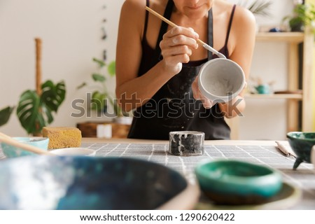 Cropped image of a woman making ceramic and pottery tableware at the workshop