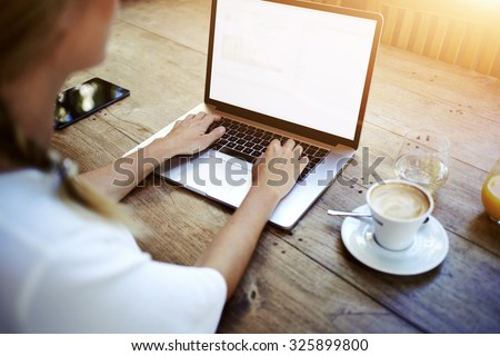 Cropped image of a woman\'s hands keyboarding on net-book while sitting at the wooden table in cafe, female student working on laptop computer with copy space screen background for your text message
