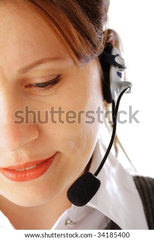 Cropped image of a young attractive business woman with headset looking down and smiling, isolated over white background