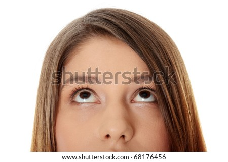 Cropped image of a young girl with her eyes looking up, isolated on white background - stock photo