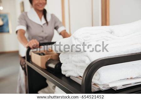 Cropped image of a young hotel maid bringing clean towels and other supplies #654521452