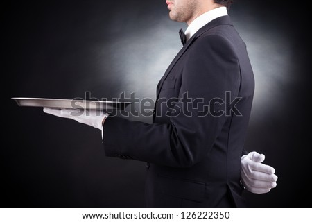 Cropped image of a young waiter holding an empty dish on black background