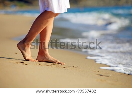 Photo of Cropped image of a young woman walking on a beach