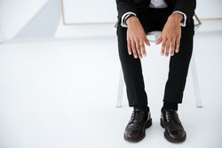 Cropped image of african business man in black suit sitting on chair in office