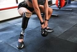Cropped image of amazing strong disabled sports woman make sport exercises with equipment in gym.