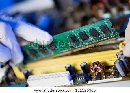 Cropped image of an electronic engineer putting RAM into the memory slot on motherboard