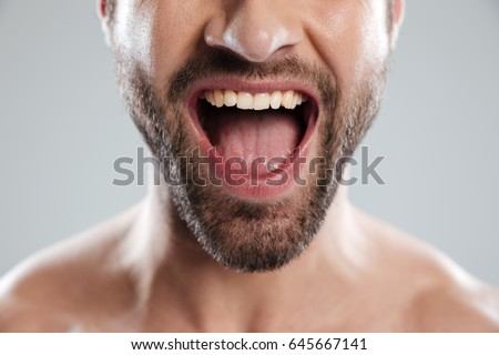 Cropped image of an excited bearded mans half face with naked shoulders and open mouth isolated over white background