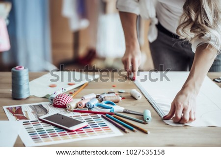 Cropped image of attractive female fashion designer is working in her workshop. Stylish woman in process of creating new clothes collection.