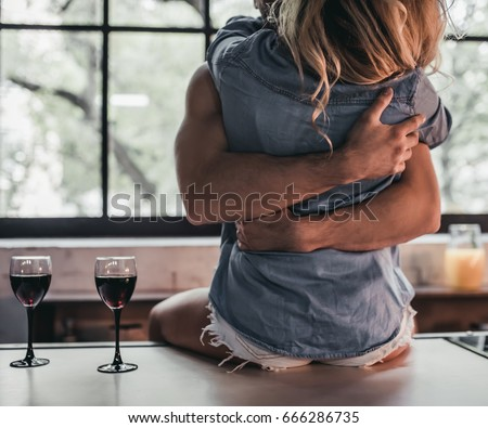 Cropped image of attractive passionate couple on kitchen. Man hugs woman while she's sitting on table.