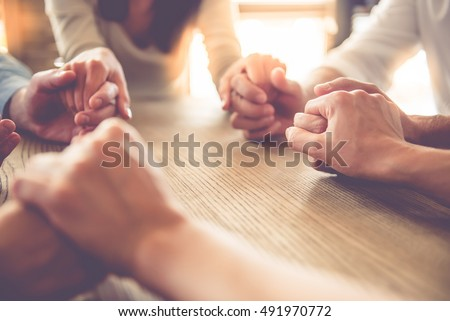 Cropped image of beautiful business team holding hands and praying while sitting in office #491970772