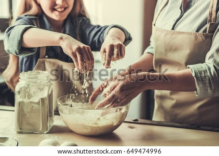 Cropped image of beautiful grandma and granddaughter kneading dough and smiling while baking in kitchen #649474996