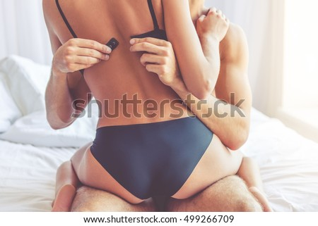Cropped image of beautiful passionate couple having sex on bed. Man is unfastening bra