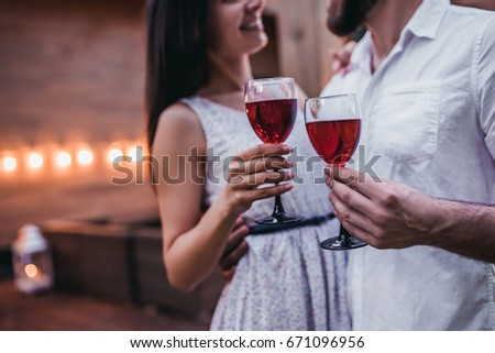 Cropped image of beautiful romantic couple on house's terrace. Drinking wine, hugging, smiling and enjoing the company of each other. #671096956