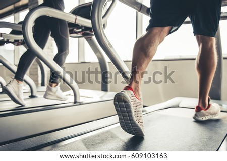 Cropped image of beautiful sports people running on a treadmill in gym