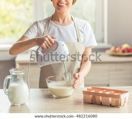 Cropped image of beautiful woman in apron smiling while mixing liquid dough for baking using an electric mixer