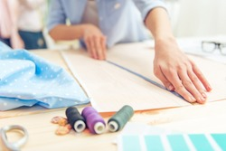Cropped image of beautiful young designer working with sketches and measure tape in dressmaking salon